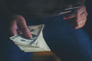 manos sosteniendo dólares con tarjeta de crédito para comprar en línea foto