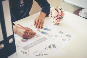 Business woman holding a pencil working with business chart photo