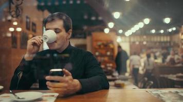 jovem empresário tomando café e digitando sms em um café. vista através do vidro com reflexo fraco da cidade video