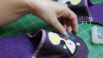 Dame faisant des chaussures en tissu fait main