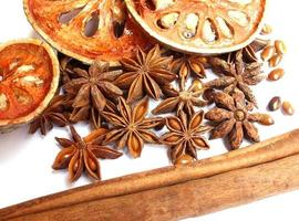 Cinnamon sticks, anise stars and dried quince on white