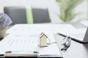 concepto de bienes raíces, modelo de casa en papel financiero foto