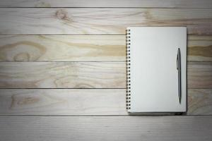 Notebook and pen on wood background with copy space photo