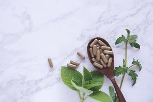 Cápsulas de hierbas medicinales en cuchara de madera con hoja verde sobre mármol blanco