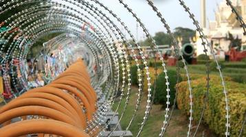 Fence topped with barbed wire photo