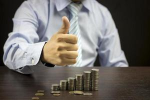 Businessman showing thumb and stacked of coins on wood table photo