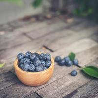 Fresh plums in a wooden bowl on old wooden background photo