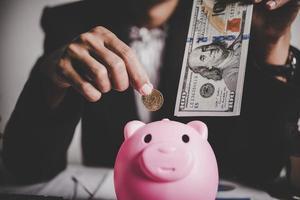Mujer poniendo billetes en una alcancía foto
