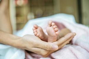 pies de bebé recién nacido en la mano de la madre foto