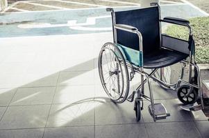 Paciente en silla de ruedas estacionada frente al hospital. foto