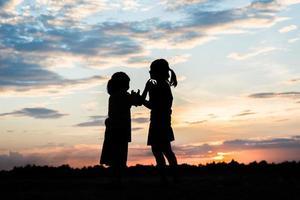 silueta de niños jugando al atardecer foto