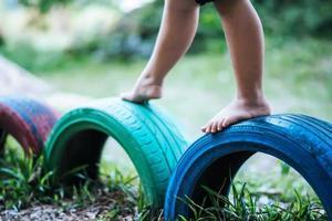 niño corriendo con neumáticos en el patio de recreo foto