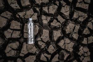 botella de agua en suelo seco con tierra seca