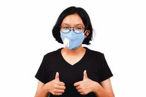 Young girl wear face mask and thumbs up for flighting Covid 19