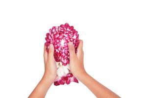 Manos con guirnalda de orquídeas sobre un fondo blanco.