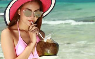 Close up of a young woman in a dress bikini drinking coconut water
