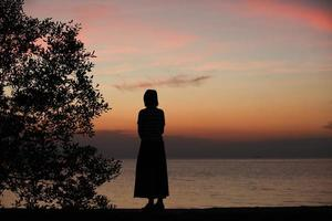 Silhouette of a woman standing alone at the seaside during sunset