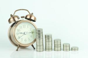 Despertador y pilas de monedas sobre fondo blanco. foto