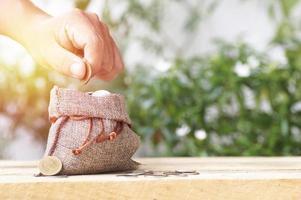 persona poniendo monedas en un pequeño saco de arpillera foto