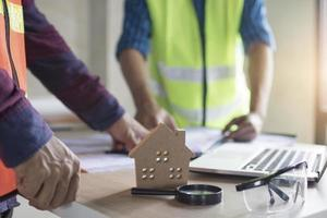 dos personas de pie en la mesa con casa modelo de madera foto