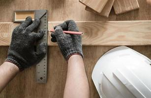 Carpenter measuring and writing on wood photo