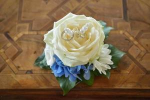 Wedding rings on white rose photo