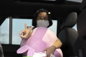 Young girl wearing a mask showing a V-sign or peace sign during COVID-19