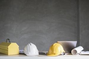 Dos cascos y herramientas de construcción en la mesa. foto