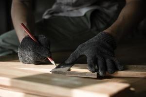 Carpenter measuring wood photo
