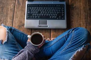 persona sosteniendo un café con una computadora portátil foto