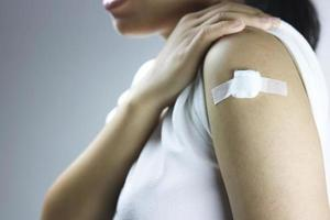 las mujeres asiáticas tienen un vendaje en el hombro después de una inyección de vacuna foto