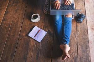 mujer sentada en el suelo con una computadora portátil foto