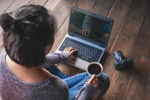 Woman working on a laptop with a coffee and a camera