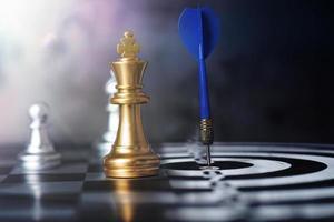 rey del ajedrez con dardo de flecha en el centro del tablero de dardos foto