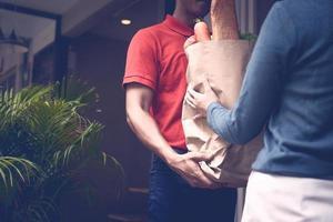 Repartidor dando víveres a los clientes.