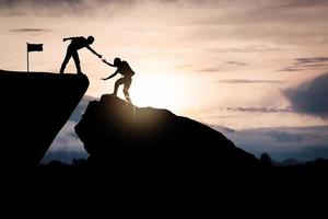 Two people helping each other climb a mountain photo