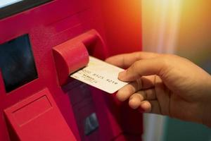 Hand putting ATM card into machine photo