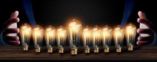 A bunch of lightbulbs in between a man's hands photo
