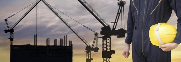 Silhouette of crane and construction worker photo