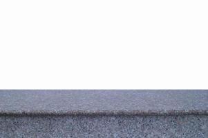 Parte superior vacía de la mesa de piedra de granito aislado sobre fondo blanco. foto