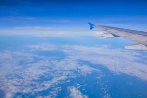 Top view blue sky with wing of airplane photo
