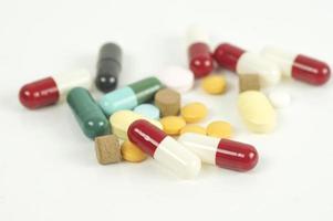 Variedad de píldoras y cápsulas sobre fondo blanco. foto