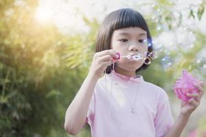 Cute Asian kid blowing bubbles in park photo