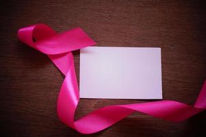 Pink ribbon and white paper on wood background photo