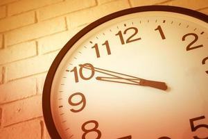un reloj en la pared de ladrillo blanco