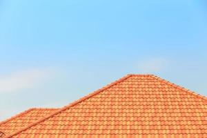 Orange tiles on a roof of a house against a blue sky background photo