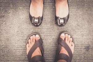 A man and woman wearing shoes standing on the asphalt concrete floor photo