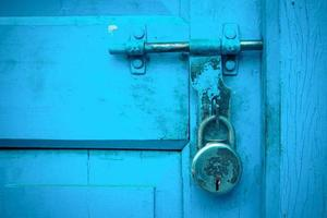 Close up of a blue wooden door with a lock