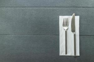 Cuchillo y tenedor en una servilleta sobre un fondo de madera