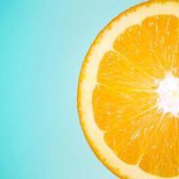Fruta naranja en rodajas aislado sobre un fondo azul. foto